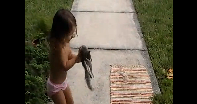 little girl playing with dead squirrel