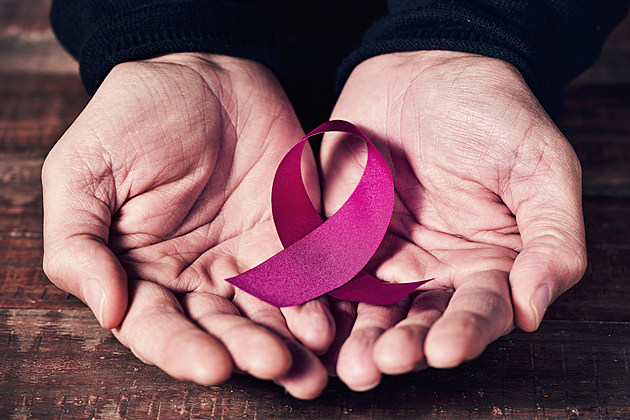 pink ribbon in the hands of a man